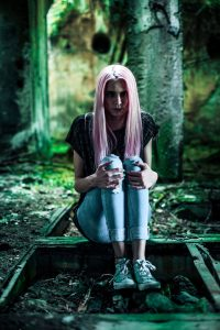 Purple highlights in straight long blonde hair; young woman sitting in dark forest