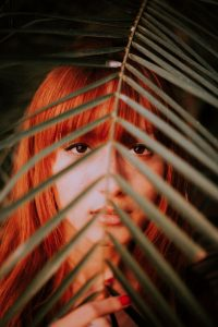 Pure Henna is a Natural Auburn Red Hair Dye for Blondes. Woman with Red Hair Looking Through a Leaf Held in Front of Her Face.