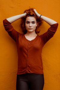organic brown hair dye; woman in rust colour long sleeve top standing against a wall with her arms touching the top of her head