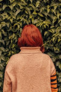 Mixing Henna, Renaissance Henna, photo of back of woman with red hair facing a green bush, wearing a beige jumper