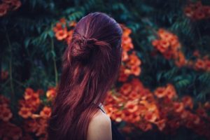 Blonde Hair Goes Dark Auburn Brown with Indigo after Henna; picture of girl with long dark auburn hair against a flower bush and dark green leaves background