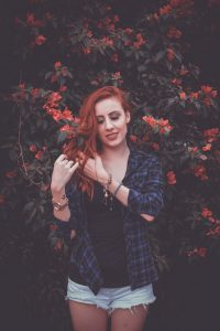 Henna turns light colour hair auburn red and darker colour hair deep auburn red brown.; woman in denim jacket standing in front of flower bush,with long auburn colour hair.