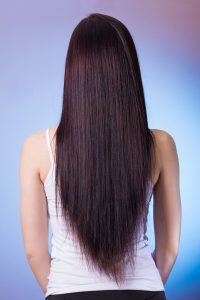 plant-based hair dye is organic, picture of back of woman with long straight dark hair wearing a sleeveless white dress