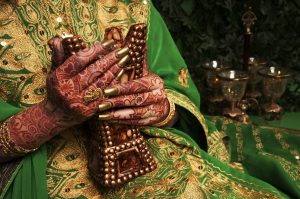 body art henna on hands decorated with indian henna and gold nails, indian bride