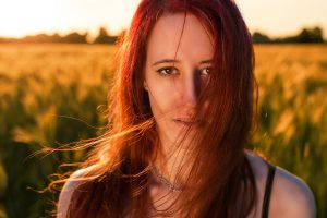 Oakwood powder or dbarrgh powder colours blonde hair light copper red; picture of woman in a field against a soft sunset glow with fine long hair glowing copper red