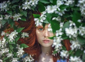 Natural beauty products, plant based, Renaissance Henna; picture of young woman with auburn hair, dace opartially obscured by green leaves and white flowers.