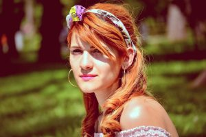 Acacia Catechu is a semi permanent hair dye which gives Copper highlights on Blonde hair.: Lady Sitting in the Sunshine with Copper Coloured Hair Secured by Colourful Headband, and Fringe Falling Across Her Face
