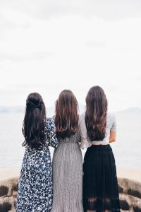 Blonde Hair Turn Brown to Black with Indigo after Henna; three ladies with long dark colour hair looking out to sea