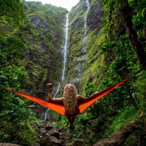 Woman with long hair down her back on red hammock facing a rock face with trickling waterfall