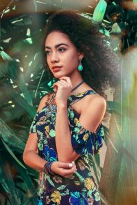 herbal hair colour is beautiful hair colour from plants; woman with natural wavy black hair standing besides a green bush, she's wearing a blue and green print summer dress and green earrings