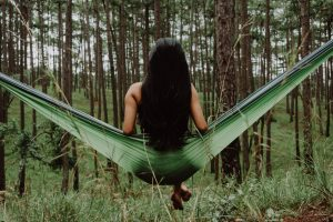 Natural hair dye from plants colours and maintains beautiful hair; woman sitting on a leaf hammock in a forest, with her long black hair down her back