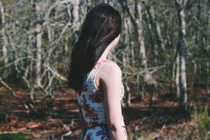 herbal hair colour from plants colours brown, & black; woman walking through forest, wearing light colour summer dress and long black hair down her back