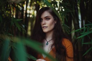 Herbal hair colour is made from plants, Renaissance Henna specialises in natural plant hair dyes ; long haired brunette standing in forest, wearing rust orange dress