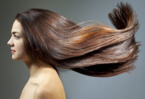 Herbal hair colours demonstrated on bare shouldered woman with long flowing brown hair  with rich but mild red tones