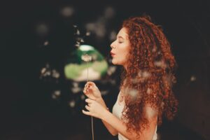 curly haired woman with long henna hair colour holding a plant and blowing