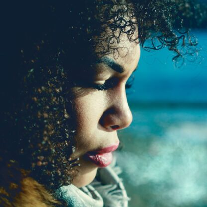 Natural black hair, profile of young black woman with curly black hair against a blue background